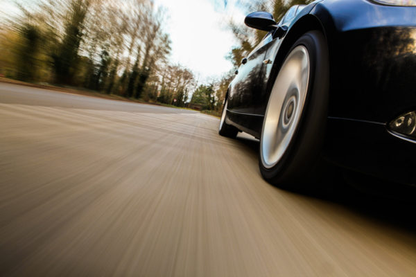 A low angle view of a car speeding down a rural road
