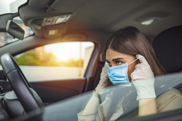 Woman puts on a facemask preparing to drive